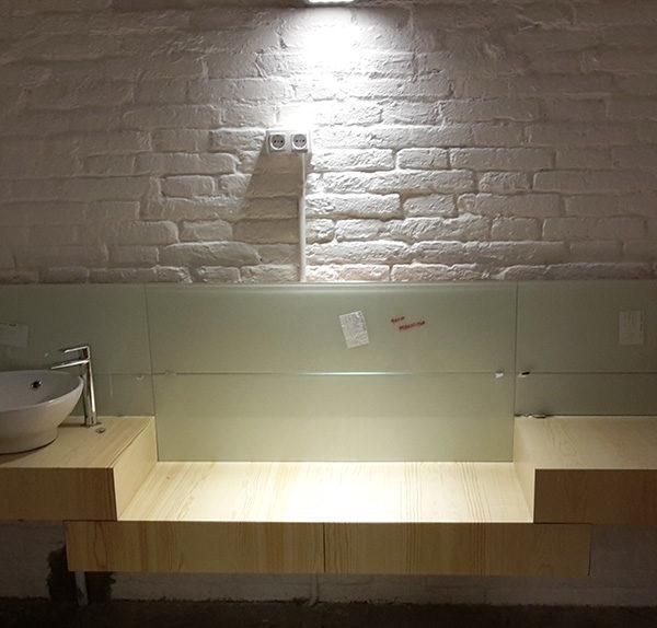 Imagen de un cuarto de baño en construcción con encimera en color madera, un sanitaro y un grifo, proyecto en construcción por Smart Llobet.