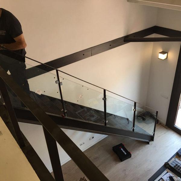 Imagen de una vivienda vista desde la planta de arriba donde muestra a una persona trabajando en unas escaleras oscuras con baranda acristalada.