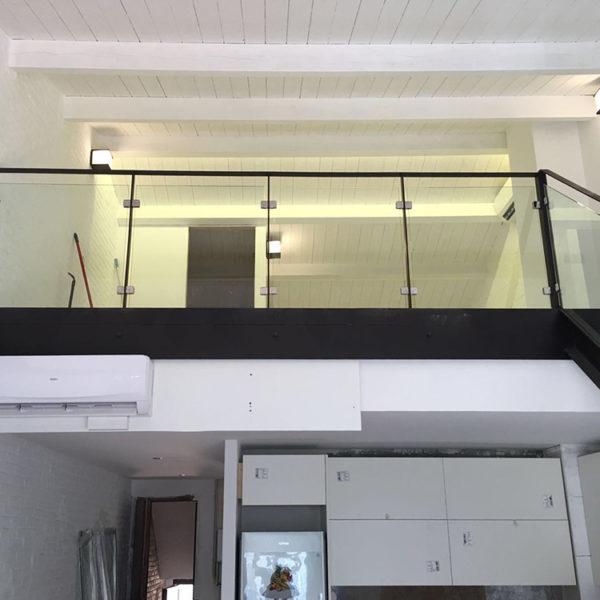 Imagen de una vivienda en dos plantas en la que se muestra unos muebles en blanco y una baranda acristalada en aluminio negro