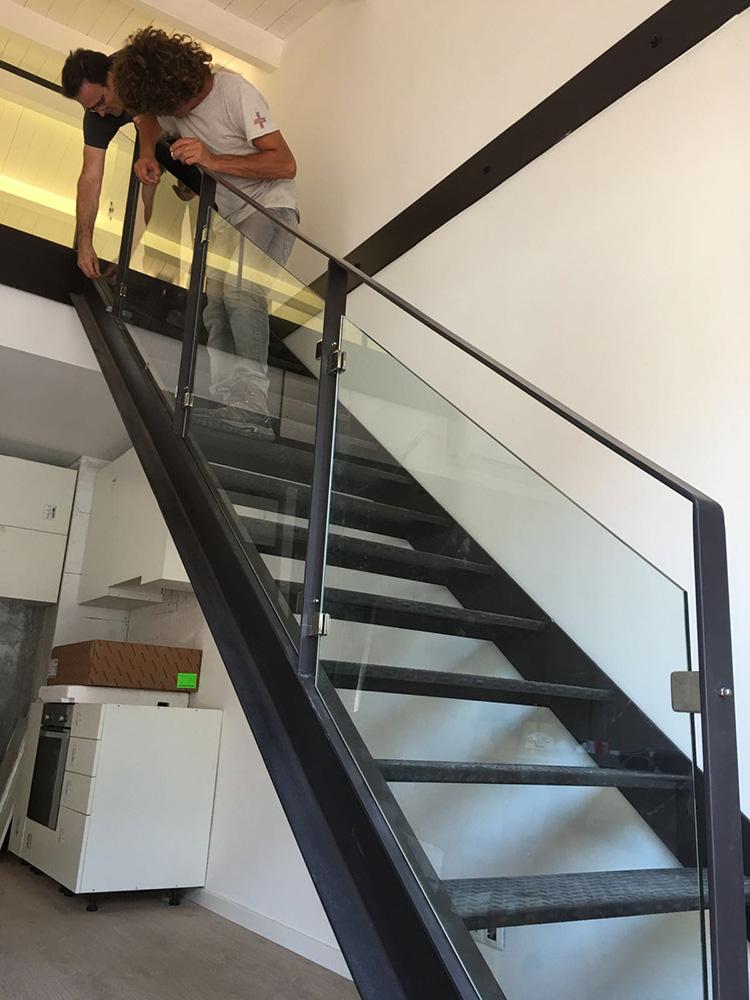 Imagen que muestra unas escaleras con baranda en aluminio y acristalada en la que incluye a dos personas trabajando en ella y unos muebles blancos en la planta baja.