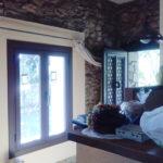 Imagen de una habitación con pared en piedra en la que se muestra una ventana en alumnio oscuro.