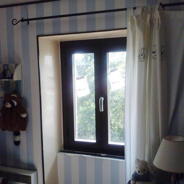 Imagen que muestra una habitanción infantil con una ventana en aluminio oscura, la pared forrada en líneas azules y blancas con detalle de peluches y cortina blancas.