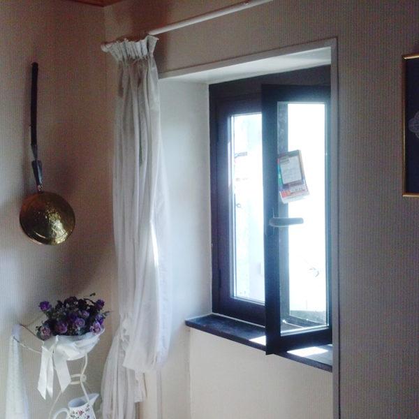 Imagen que muestra una habitación con detalle de una ventana de alumnio con unas cortinas blancas recojidas y al lado un ramo de flores de color violeta.