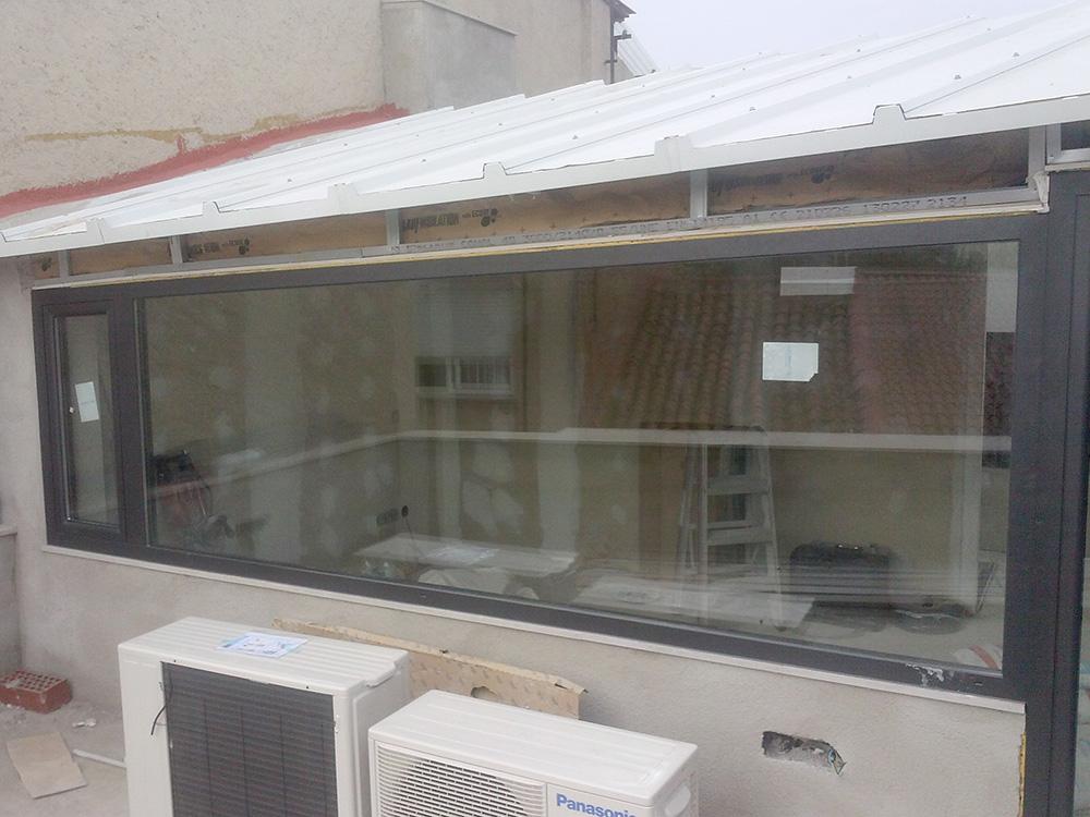 Imagen que muestra una terraza cerrada en cubierta acristalada y de alumnio oscuro obras realizada por Smart Llobet.