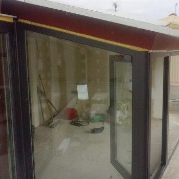 Imagen de una terraza superior cerrada por una cubierta acristalada con una puerta de entrada, obra realitzada por Smart Llobet.