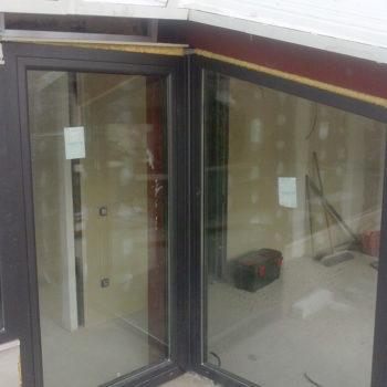 Imagen con detalle de una cubierta cerrada acristalada de alumnio en una terraza, las obras están realizadas por Smart Llobet.