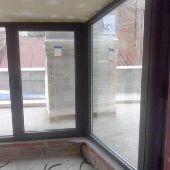 Imagen que muestra un espacio interior en una terraza cerrado por una cubierta en cristal y aluminio, obra realitzada por Smart Llobet.