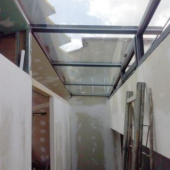 Imagen que muestra un pasillo en obras en la que el techo es acristalado, las obras están realizadas por la empresa Smart Llobet.