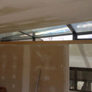 Imagen que muestra un espacio en obras con una parte del techo en cristal y alumnio, obra realitzada por Smart Llobet.