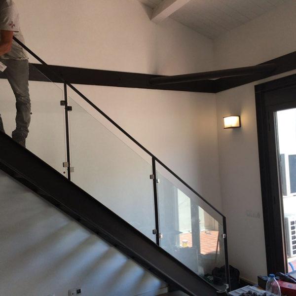 Imagen que muestra unas escaleras acristalada y en alumnio negro de una vivienda en la que hay una persona de Smart Llobet trabajando.