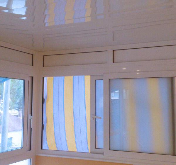 Imagen con detalle de ventanas y techo en alumnio blanco se muestra unos toldos en tonos azules y amarillos.