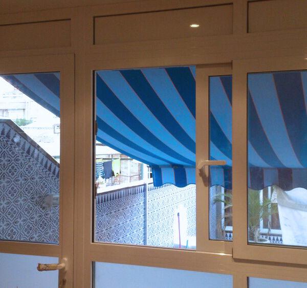 Imagen que muestra una ventana y puerta en alumnio blanco con detalle de un toldo de rayas azules projecta realizado por Smart Llobet.