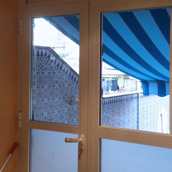 Imagen con detalle de una puerta en alumnio blanco con toldo de rayas en tonos azules, trabajo realizado por Smart Llobet.