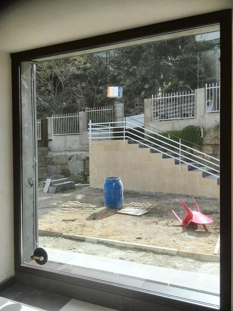 Imagen en la que muestra una ventana con vistas a la entrada de una casa con escaleras, un bidón azul y una silla roja, la colocación de la ventana de aluminio la realizó Smart Llobet.