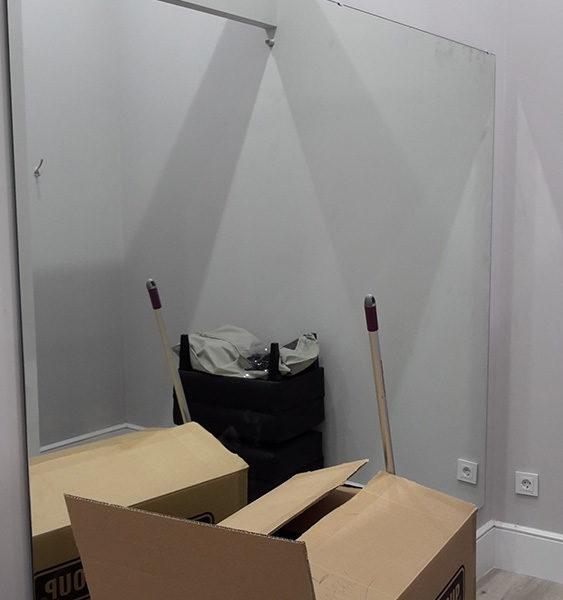Imagen con detalle de una sala con espejo en la pared y cajas de cartón, en estado de obras por Smart Llobet.