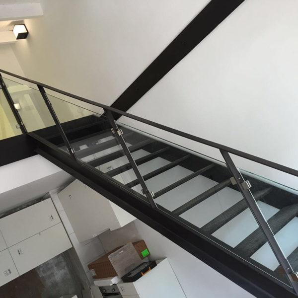 Imagen que muestra una vivienda en dos plantas con escaleras de alumnio y baranda acristalada Trabajo por Smart Llobet.