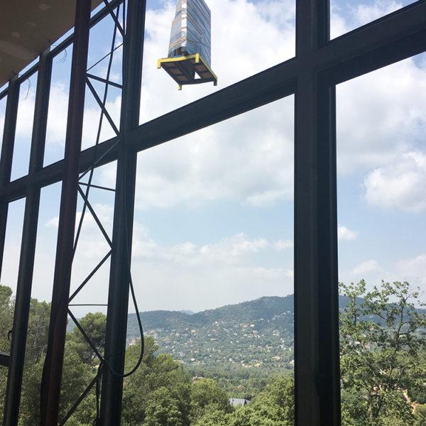 Imagen que muestra grandes ventanas hacia un paisaje de arboleda en la que se muestra el transporte de material a través de una grua.