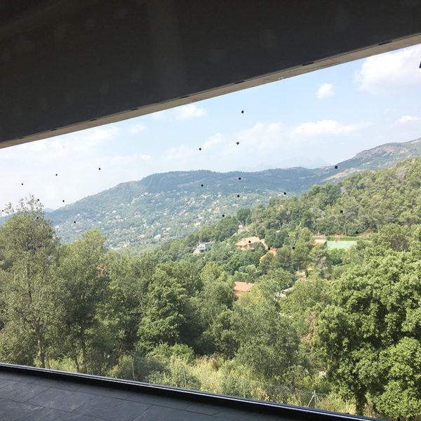 Imagen que muestra una gran ventana donde se puede ver un paisaje de arboleda, el edificio de la Localidad Matadepera en construcción por Smart Llobet.