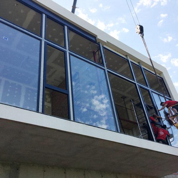 Imagen que muestra a unos trabajadores montados en un montacarga para la colocación de ventanas trabajo que se realiza en un vivienda de Matadepera.