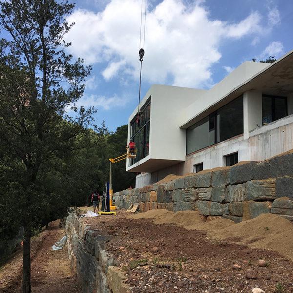 Imagen que muestra una casa donde están colocando mediante un montacarga y grua las ventanas en la localidad de Matadepera.