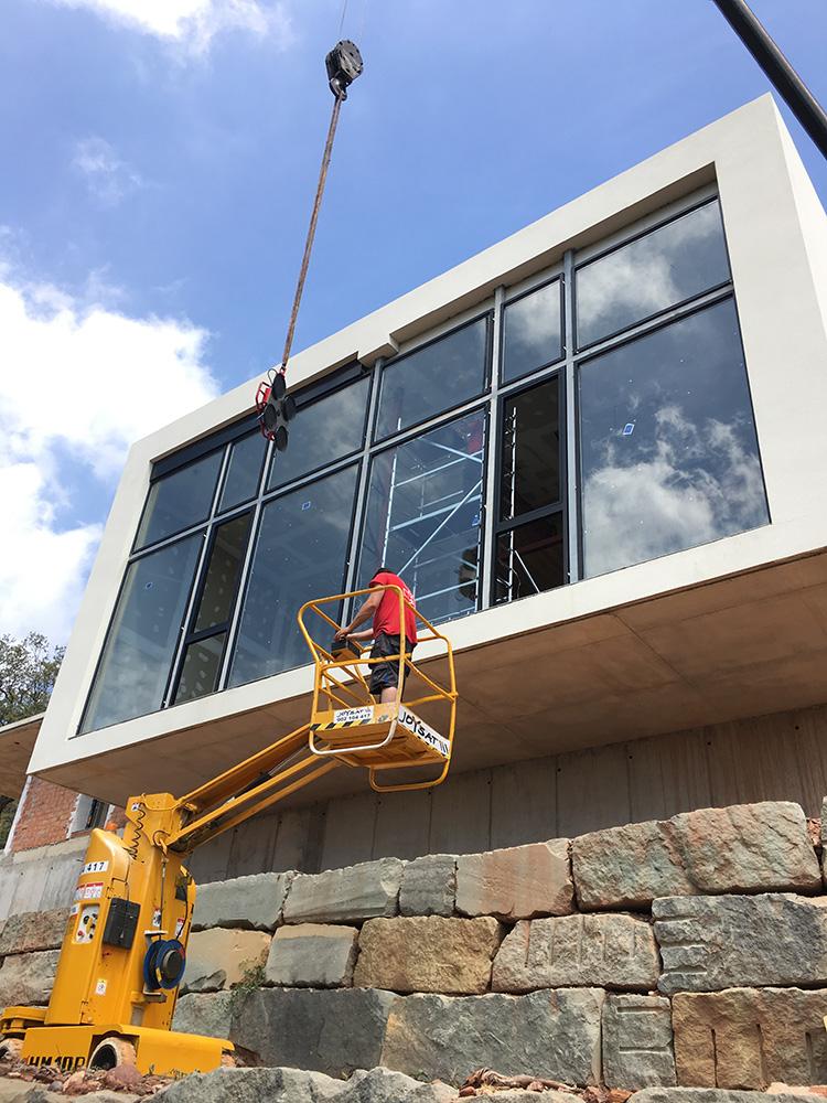 Imagen que muestra la planta de una casa encima de un bloque de piedras y la colocación de ventanas a través de un montacarga, trabajo realizado por Smart Llobet.