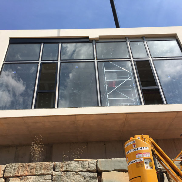 Imagen vista desde abajo de unas ventanas de la planta de una casa y una persona subida en un montacargas amarillo, trabajo realizado por Smart Llobet.